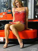 Six Inch Heels, Melanie in red dotty lingerie by a racing car.