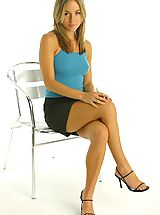 Melanie sitting in a chair wearing a tight blue top and a black mini skirt with white lacy underwear