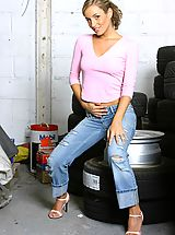 Secretary Pics: Melanie looking beautiful posing in a car workshop next to a stack of tyres wearing a tight pink top with denim jeans and blue lingerie.