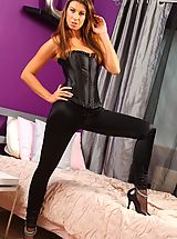 Sexy brunette shuts herself in her bedroom and gives a sexy striptease out of her tight black corset and leggings.