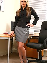 Busty Secretary, Candice wearing a black blouse with a grey skirt and grey stockings.