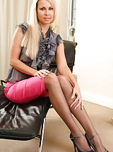 Gorgeous blonde wearing a grey opaque blouse with a long pink skirt.