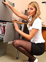 Darcy strips out of her office clothes down to her black thong and stockings.